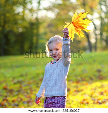Happy little child, cute toddler girl with curly blonde hair wearing yellow jacket playing with colorful leaves in park on sunny warm autumn day - stock photo