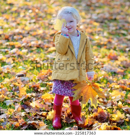 Happy little child, cute toddler girl with curly blonde hair wearing yellow jacket playing with colourful leaves in park on sunny warm autumn day - stock photo