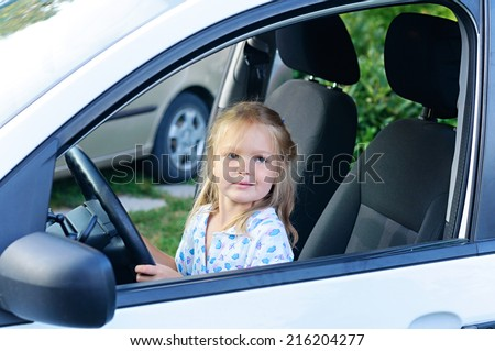 Happy little child, funny blonde toddler girl sitting of the car on driver seat holding steering wheel.  - stock photo