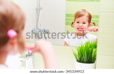 Happy little child girl brushing her teeth toothbrushes in the bathroom before the mirror - stock photo