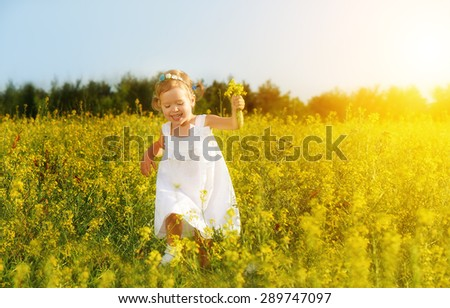 happy little child girl in a white dress running on field with a bouquet of yellow flowers, wildflowers - stock photo