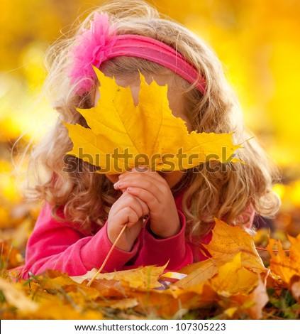 Happy little child in autumn park - stock photo