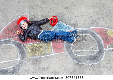 Happy little child of four years having fun with race car picture drawing with colorful chalks. Creative leisure for children outdoors in summer. Kid boy dreaming to be a racer - stock photo