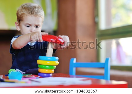 happy little child play game and have fun, education lessons in colorful kinder garden playground indoors - stock photo
