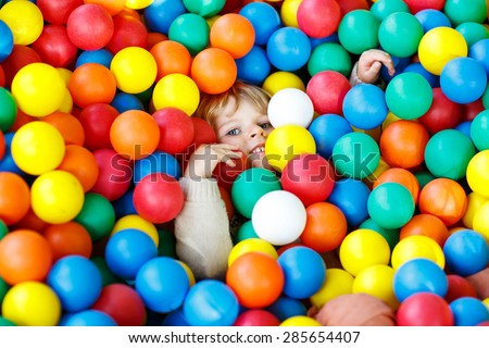 Happy little child playing at colorful plastic balls playground high view. Kid boy having fun indoors. - stock photo
