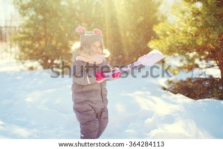 Happy little child playing in sunny winter day - stock photo