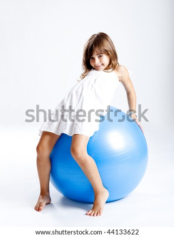 Happy little child playing with a big blue ball - stock photo
