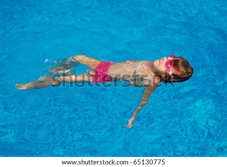 Happy little child swimming on her back in pool. Active girl swims and having fun. Child sport on summer vacation - stock photo