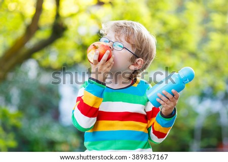 Happy little child with books, apple and drink bottle on his first day to elementary school or nursery. Outdoors.  Back to school, kids, lifestyle concept. Boy eating fruit - stock photo