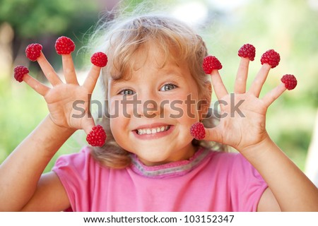 Happy little child with raspberry outdoors - stock photo