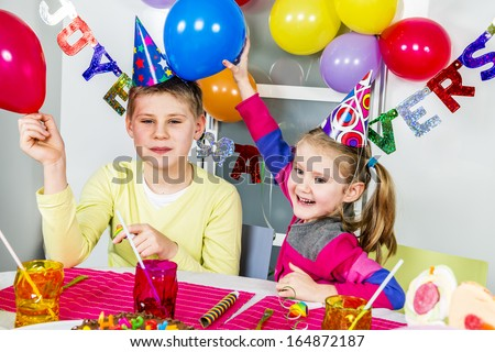 Happy little children are having fun in a birthday party  - stock photo