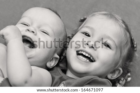 happy little children brother and sister hugging lying ( black and white ) - stock photo