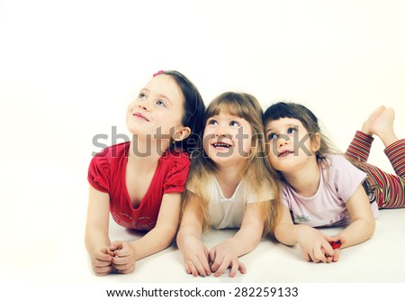 Happy little children lie on the floor - stock photo