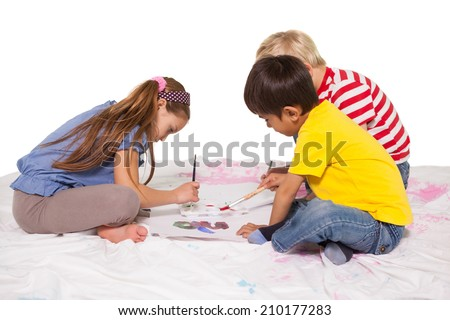 Happy little children painting on the floor on white background - stock photo