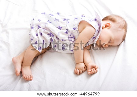 Happy little cute girl sleeping on the bed - stock photo