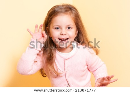 happy little girl a on yellow background - stock photo