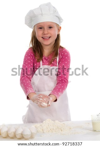 Happy little girl adding eggs in the flour - stock photo