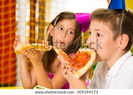 Happy little girl and boy eat pizza - stock photo