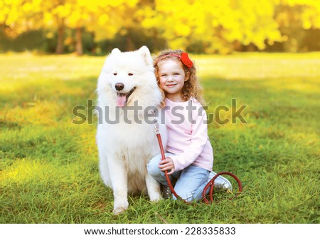 Happy little girl and dog having fun outdoors in warm sunny day - stock photo