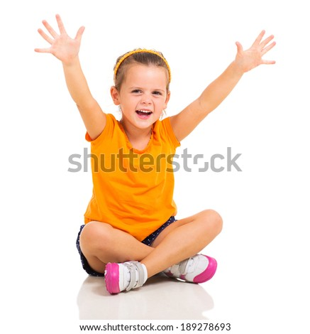 happy little girl arms up while sitting on floor isolated on white background - stock photo