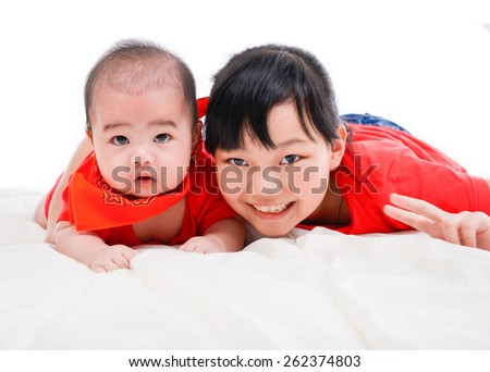 happy little girl ,baby on the floor laying on in bed - stock photo