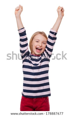 Happy little girl. Cheerful little girl keeping arms raised and smiling while standing isolated on white - stock photo