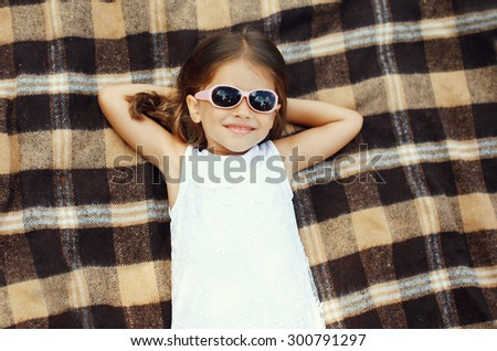 Happy little girl child in sunglasses lying resting on the plaid, top view - stock photo