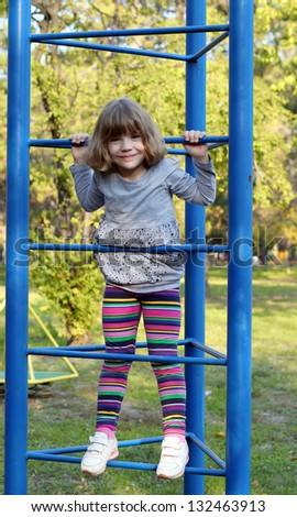 happy little girl climb on park playground - stock photo