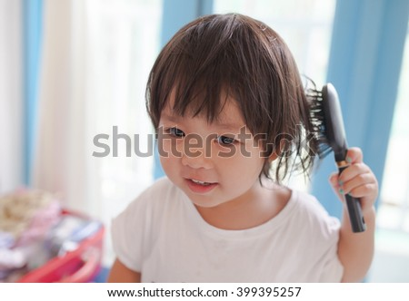 Happy little girl combing her hair at the hotel. - stock photo