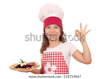 happy little girl cook with crepes and ok hand sign - stock photo