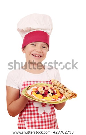 happy little girl cook with crepes on plate - stock photo