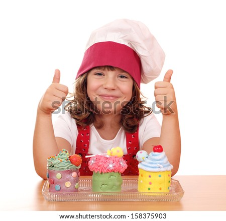 happy little girl cook with cupcakes and thumbs up - stock photo
