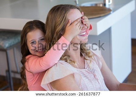 Happy little girl covering her mother eyes at home - stock photo