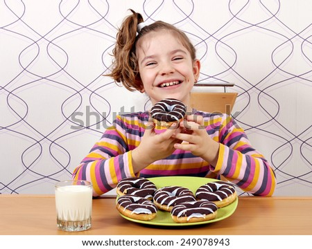 happy little girl eat sweet chocolate donuts - stock photo
