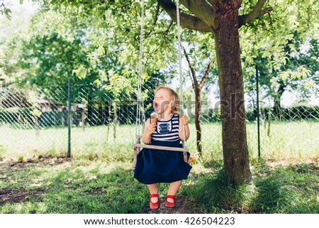 Happy little girl eating ice cream while on the swing in the yard - stock photo