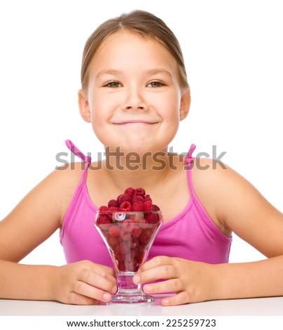 Happy little girl eats raspberries, isolated over white - stock photo