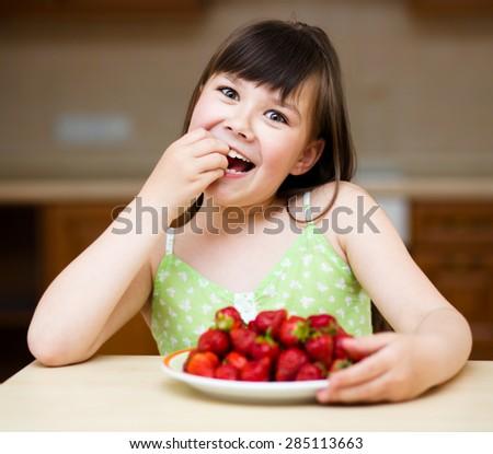 Happy little girl eats strawberries - stock photo