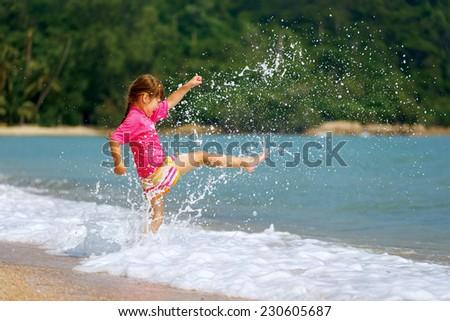 Happy little girl enjoying holiday beach vacation in Thailand. - stock photo