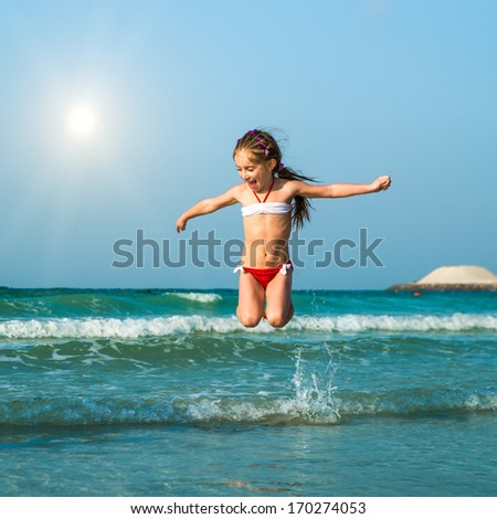 Happy little girl having fun in the sea - stock photo