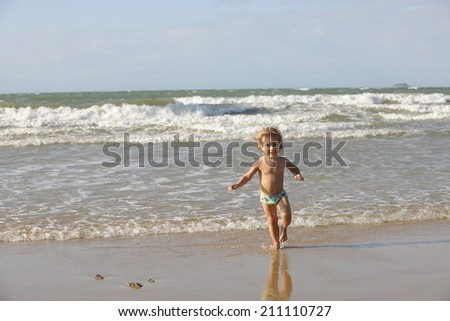 Happy little girl having fun on the beach. - stock photo