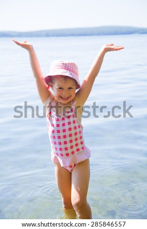 Happy little girl having fun, swimming  at shallow water - stock photo