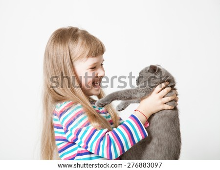 Happy little girl holding  a cat on neutral background - stock photo
