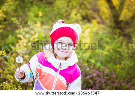 happy little girl holding a dandelion in the forest - stock photo