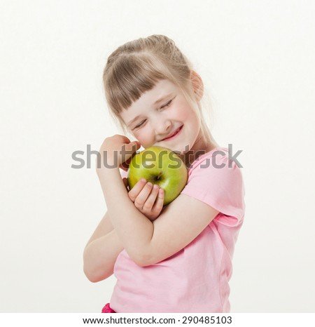 Happy little girl holding a green apple, white background - stock photo