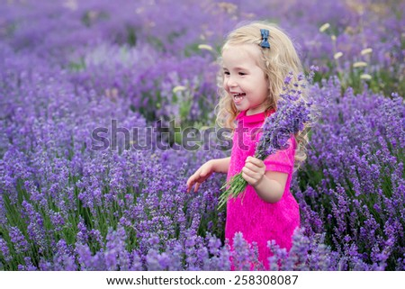 happy little girl in a field holding a bouquet of lavender - stock photo