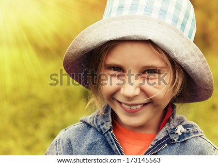 Happy little girl in a hat on a background of nature. - stock photo