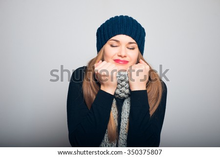 happy little girl in a scarf wraps, winter concept, studio photo isolated on a gray background - stock photo