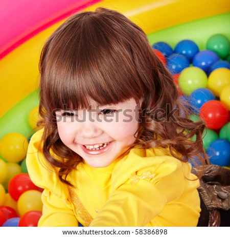 Happy little girl in group colourful ball. - stock photo