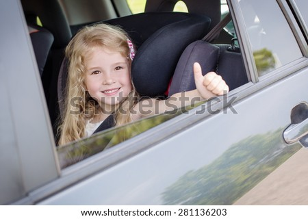 happy little girl in the car summer - stock photo