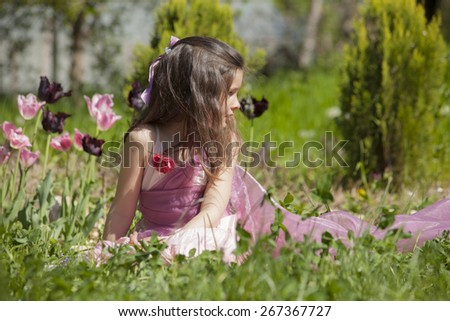 Happy little girl in the garde? playing on the grass - stock photo
